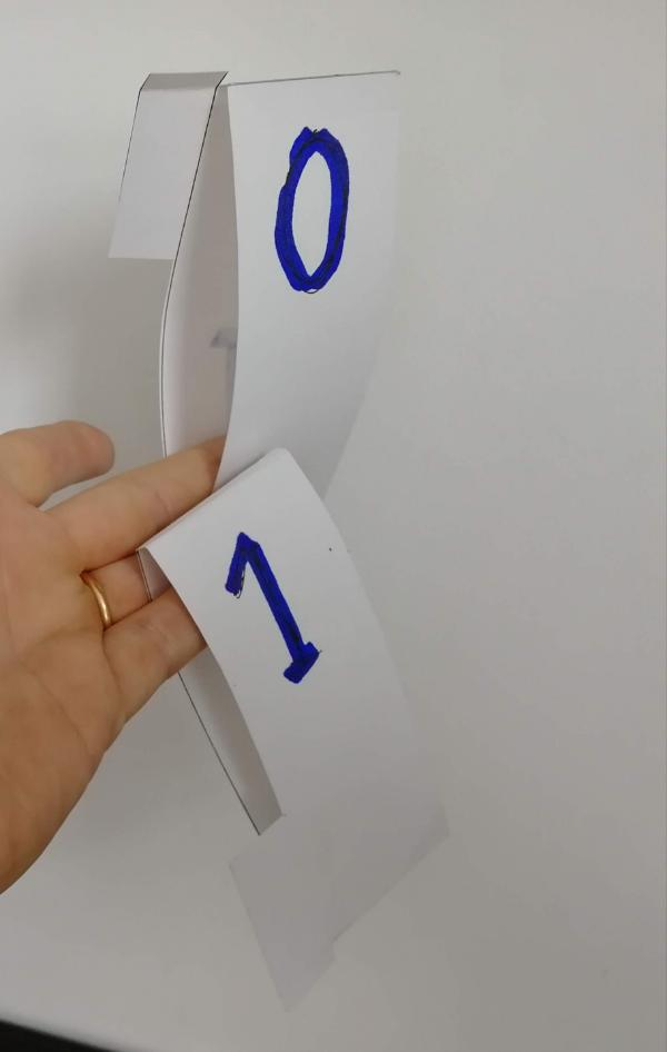 Une simple languette de carton, repliée et collée, échancrée du côté du 1 pour propager la retenue, à enfiler sur une réglette.